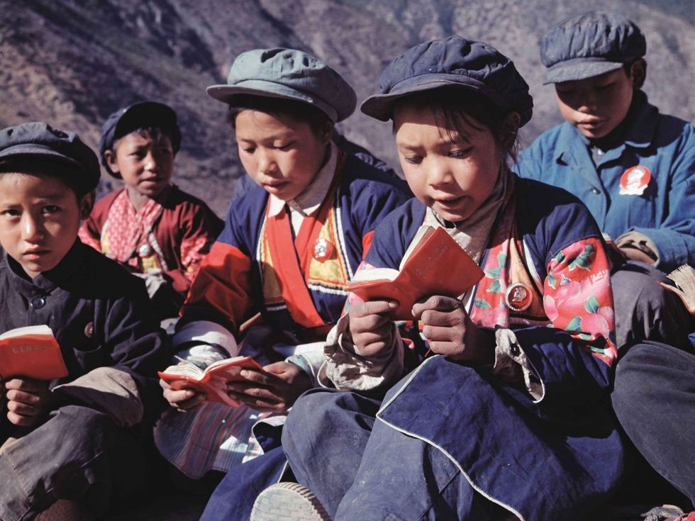 """1960至1980年代,人们的阅读发生了翻天覆地的变化。从每个人手捧""""红宝书""""、排队购买《毛主席语录》、亲友结婚时用《毛选》作为礼物馈赠,到改革开放后,人们对知识、文化生活的渴求井喷似地爆发。尤其是1977年,中断了10年的高考制度得以恢复,消息传出,人们积极学习文化知识,备战高考的热情高涨。科学、文化的价值被重新认可,中国终于开始进入了一个尊重知识、尊重人才的时代。图为1970年,云南中甸,新联大队少年阅读《毛主席语录》。"""