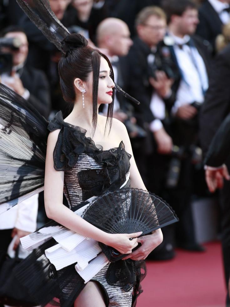"""又到一年戛纳时,众女星红毯上争奇斗艳,中国女星的新闻也不断,除了穿""""国旗装""""蹭红毯的网红,还有一位中国艳星造型也很雷人。图为戛纳红毯上的蓝燕。(图源:VCG)"""